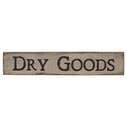"""Dry Goods Sign is made from wood and features distressed edges and bold, black lettering. Measures 18″ long by 3½"""" high."""