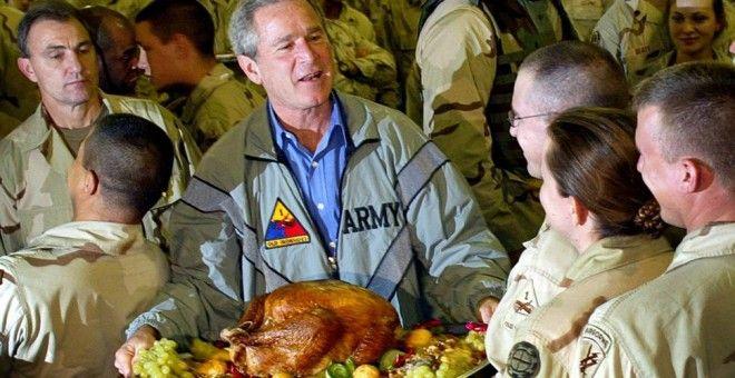 El expresidente de EEUU, George W. Bush, posa para una foto portando un pavo de Acción de Gracias durante su visita a las topas estadounidenses en Bagdad, el 27 de noviembre de 2003. El pavo resultó ser una recreación falsa de plástico.- TIM SLOAN (AFP)