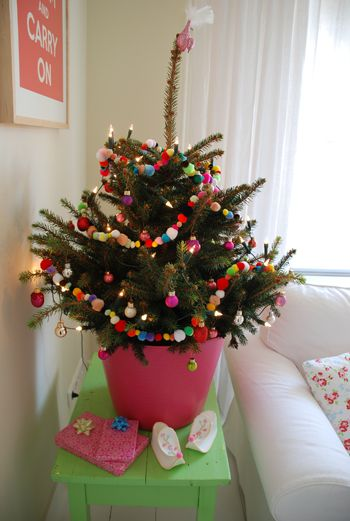 a little christmas tree in a pink pail with pom-pom garland                                                                                                                                                                                 More