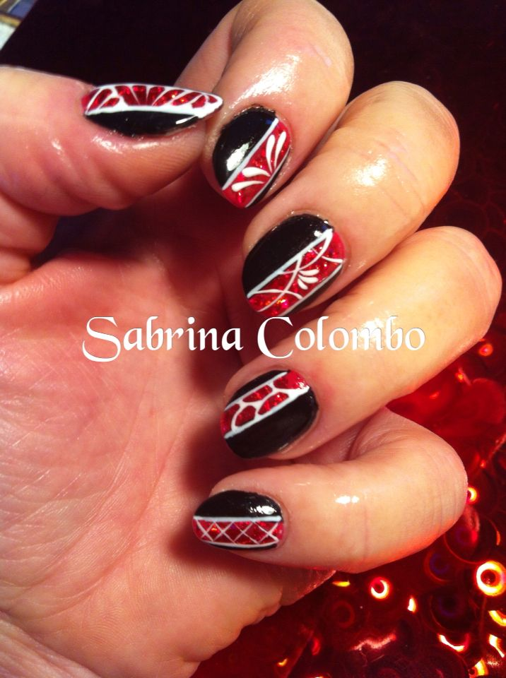 Copertura in gel su unghie naturali deco styline nei toni rosso bianco e nero