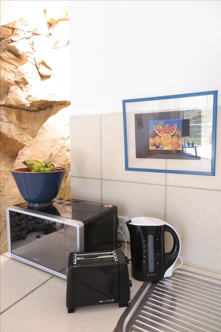 There is a kettle, toaster, microwave, gas stove, electric oven and kitchenware