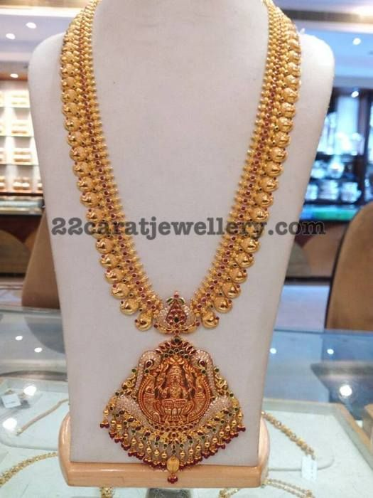 Plain paisley motifs embellished 22 carat gold long chain with simple spinal rubies and Two step Lakshmi antique pendant, highlighted wit...