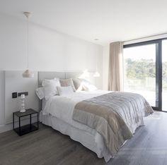 Detalle de dormitorio en vivienda unifamiliar situada en Ibiza íntegramente proyectada por Natalia Zubizarreta Interiorismo. Pavimento de roble grisáceo, cabecero lacado en blanco y tapizado, ropa de cama blanca y de colores naturales. Luminarias Pleat Box de Marset en blanco. Mesillas negras.