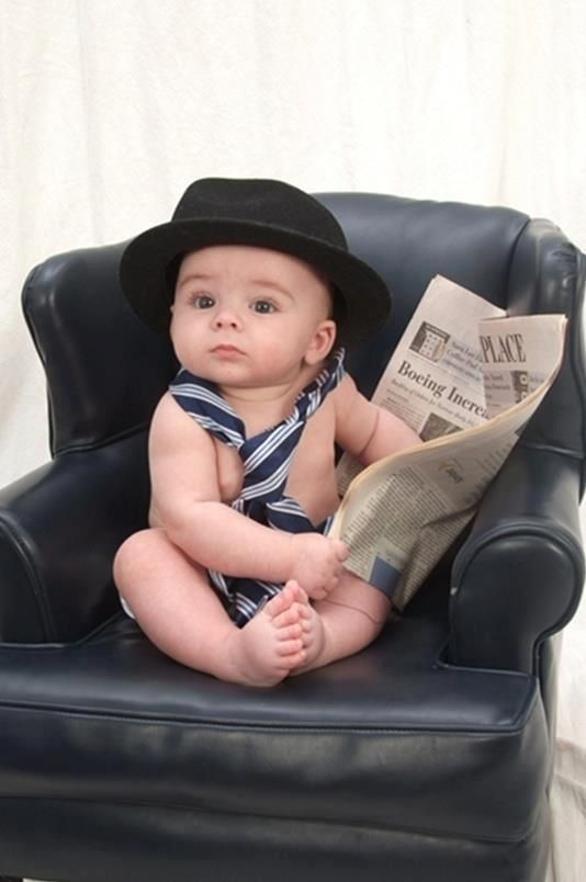 Adorable little man reads the newspaper. Hat, tie, and newspaper