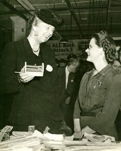 """Donated by Rosanna Wambach. Bernice Palmer, right, unknown to donor, and Eleanor Roosevelt, left. Bernice worked at Packard in Detroit, MI. """"Birthday greetings are delivered personally by Mrs. Eleanor Roosevelt to Bernice Palmer (above), Packard war worker who suggested more production shortcuts than any woman employee."""""""