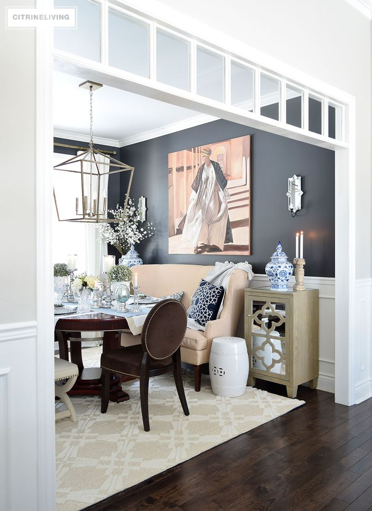 Elegant dining room with black walls and blue and white chinoiserie accents. White transoms add architectural interest. A simple Easter or Spring tablescape with metallic accents adds sophistication.