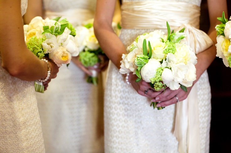 The bride's choice of a palette of fresh spring green, ivory, creams and white is reflected to perfection in the bridesmaids' bouquet of Caramel garden rose, Amelia rose, green parrot tulip, white peony, and viburnum hand tied and wrapped in cream satin ribbon.
