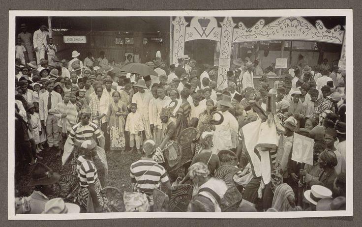 Anonymous | Deelnemers aan een optocht en publiek voor een restaurant, Anonymous, 1920 - 1930 | Achter de optocht bevindt zich een openluchtrestaurant genaamd Hadji Djansiti. Links van dit opschrift is een kroon met een W afgebeeld, mogelijk verwijzend naar koningin Wilhelmina. Vermoedelijk wordt de optocht gehouden ter gelegenheid van Koninginnnedag. In het restaurant een bord met daarop Hotel Sappangdjang. Geheel links is een bord met het opschrift Soedi Singgah. Onderdeel van Familiealbum…