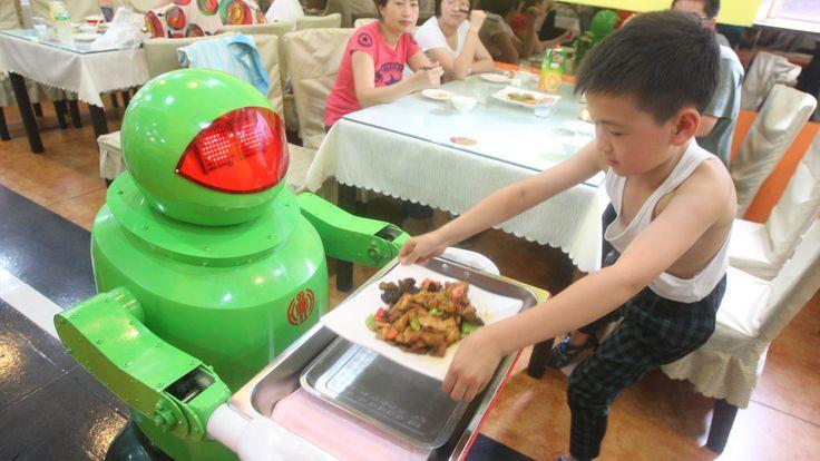 """In een restaurant in de Chinese stad Harbin werken twintig robots. Als je binnenkomt, glijdt er een robot op je af met de woorden: """"Hallo aardbewoner, welkom in het robotrestaurant."""" Bij het groente snijden krijgen de robots hulp van de gewone koks, maar verder doen de machines alles zelf: friet bakken, rijst koken en bedienen."""