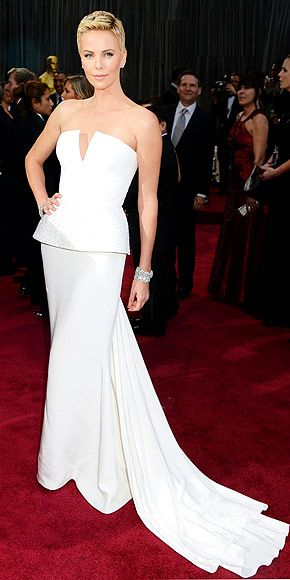 """Who needs a statue when you look this statuesque? Charlize makes the most dramatic entrance at the Oscars thanks to her edgy crop, Harry Winston jewels and this pristine white peplum Dior Haute Couture, which prompted her to say, """"I sometimes just really feel like a princess."""""""