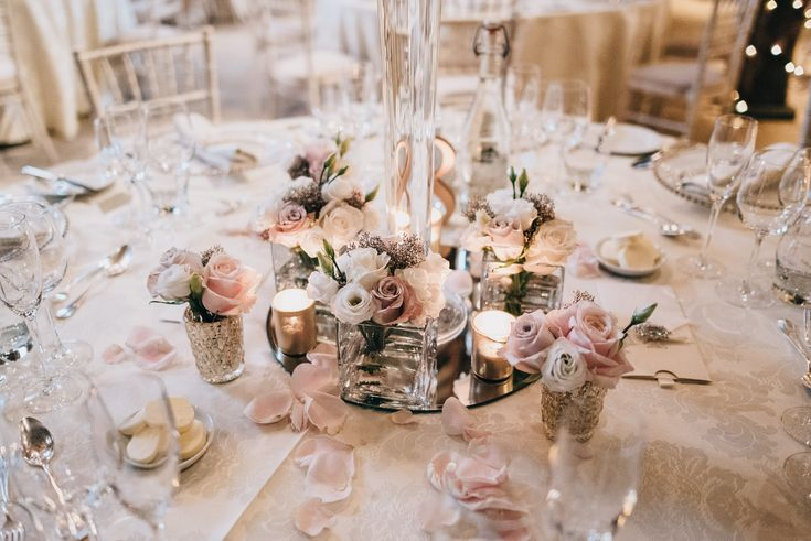 Low cluster wedding centrepieces. Dusky pink and ivory flowers. Menta roses, sweet avalanche roses, orchids. Great Fosters wedding. Surrey wedding flowers by Boutique Blooms floral design.
