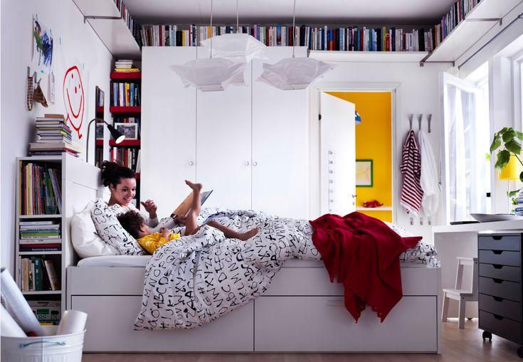 Una mamma e la sua bambina sedute su uno spazioso letto bianco in una camera luminosa e moderna circondata da libri - IKEA