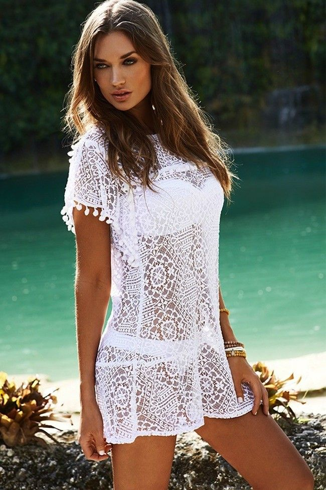 Pily Q Water Lily Pom Pom White Dress at Pesca Boutique. Sexy and Fun the same time sheer lace Crochet tunic with white pom pom detai along the sleeves. It is the perfect cover up to throw over any of your swimsuits. - Price: $144.00