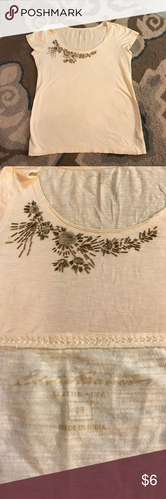 Beaded Woman's t shirt size Large His is a cream colored woman's tee shirt blouse size medium. It has a small beaded design . A few beads do look to be missing, but it is unnoticeable. The brand is Eddie Bauer . Eddie Bauer Tops Tees - Short Sleeve