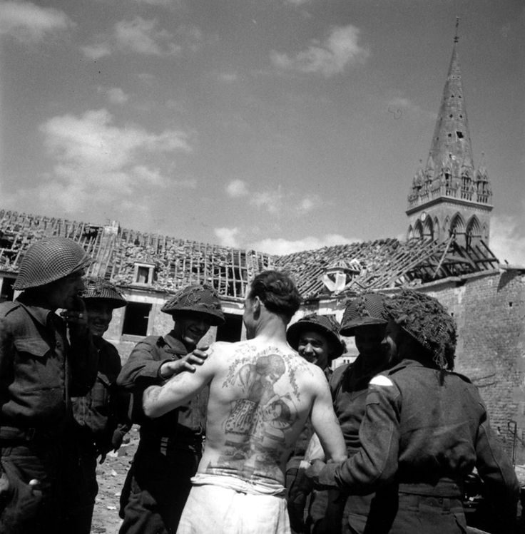 Members of Headquarters Company, Regina Rifles, admire a tattooed Frenchman. 15 June 1944. (National Archives of Canada PA 169259)