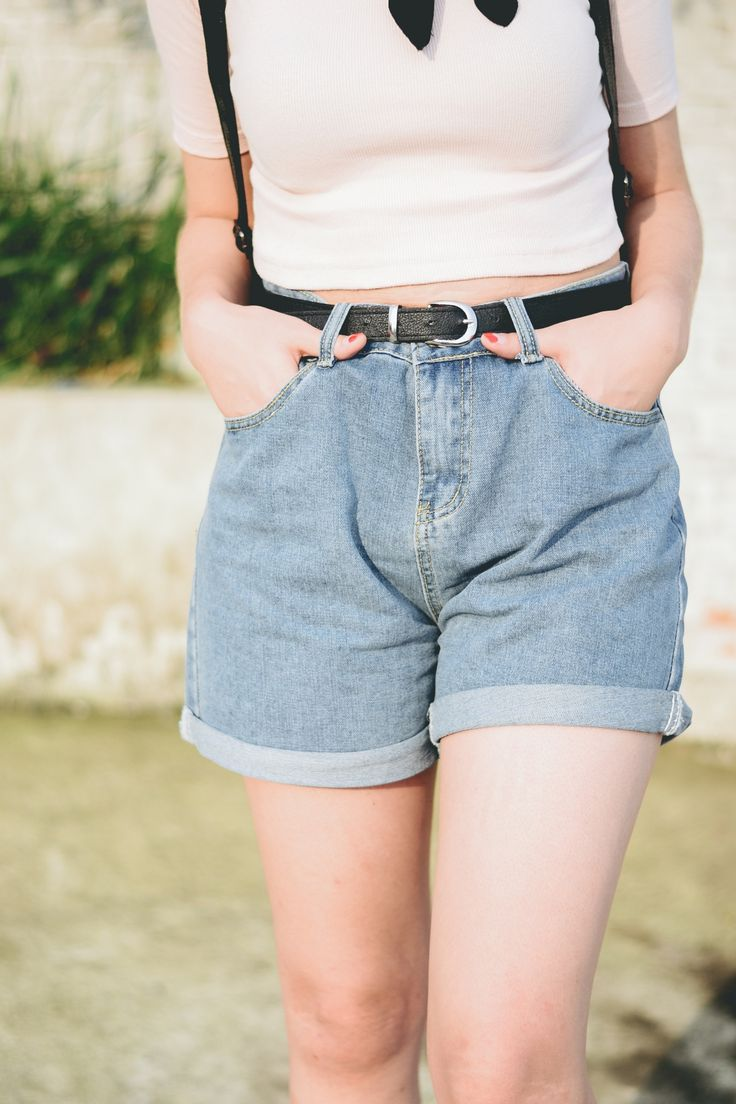 Look de verão com short jeans cintura alta, bota de cano curto, babylook, mochila e bandana no pescoço.