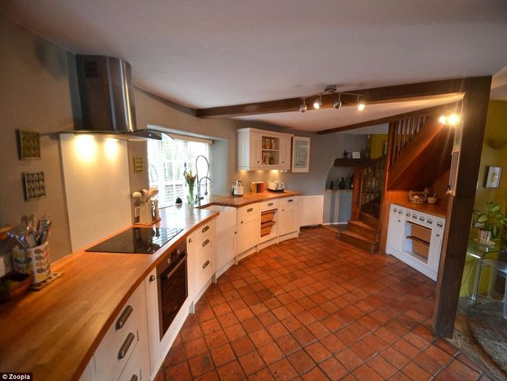In a round house you need a bespoke kitchen: the units have oak tops, white bottoms, terracotta tile floor making the most of the available space....