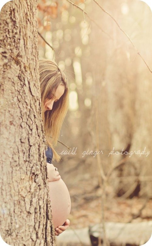 peek a belly. Maternity photo in field. Cute pose idea -- for outside when there's no wall! Or maybe behind an industrial wall!
