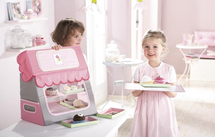 """Kaufladen """"Kuchenglück"""" - Hier gibt es frisches Gebäck und schön dekorierte Pralinen! Dieser niedliche Kaufladen für süße Leckereien ist perfekt für alle Nachwuchsbäcker. Er passt in jedes Kinderzimmer und kann dank der Tragegriffe an der Seite auch leicht mitgenommen werden. Die Köstlichkeiten aus Stoff liegen in fünf Auslagenboxen. Das Tablett verschließt beim Transport die hintere Öffnung und kann prima zum Servieren des Gebäcks verwendet werden."""