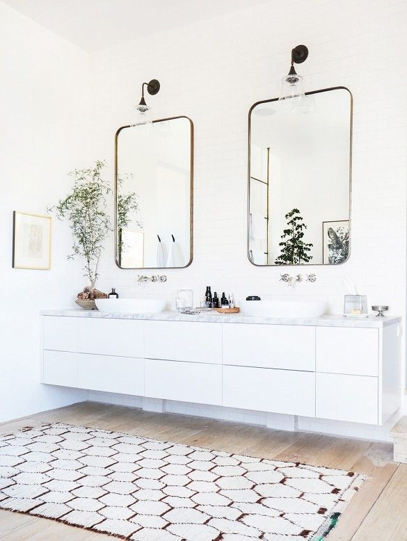 White bathroom with two mirrors and sinks: