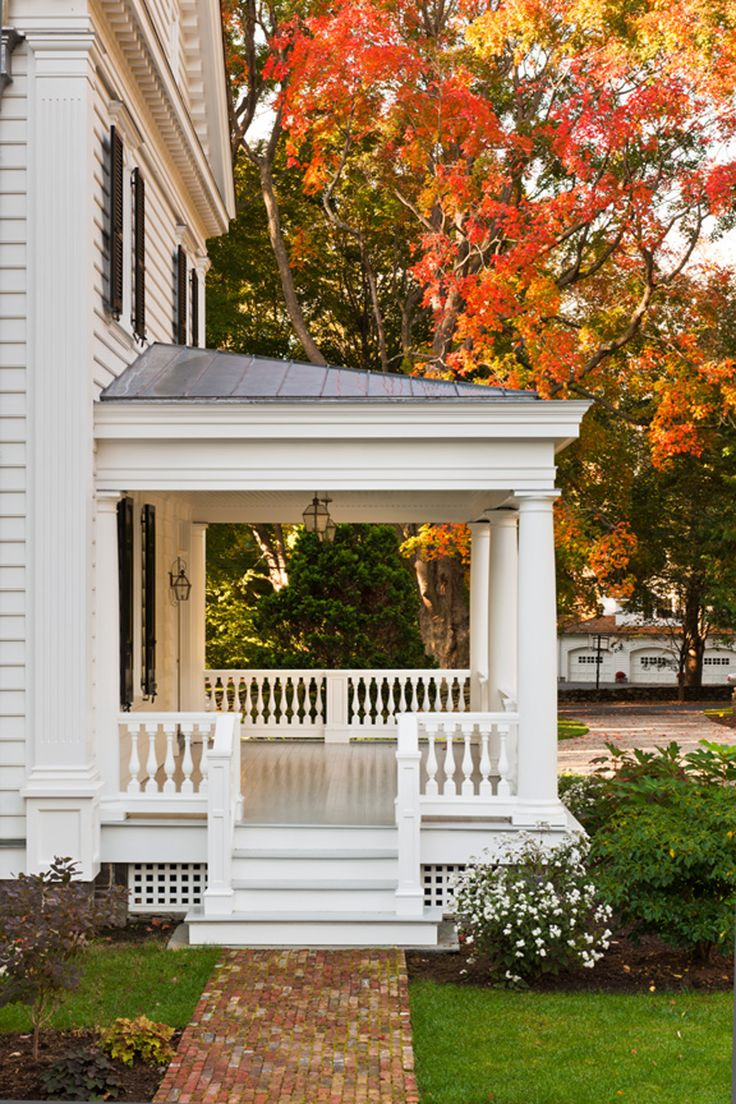 A covered porch with pristine, classical detail make this front entrance warm and inviting.