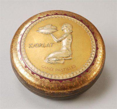Rond chocoladeblik van Tjoklat Camee Pastilles, bruin en goud blik met op de deksel in wit een reliëf,een oosterse vrouw geknield met een schaal.