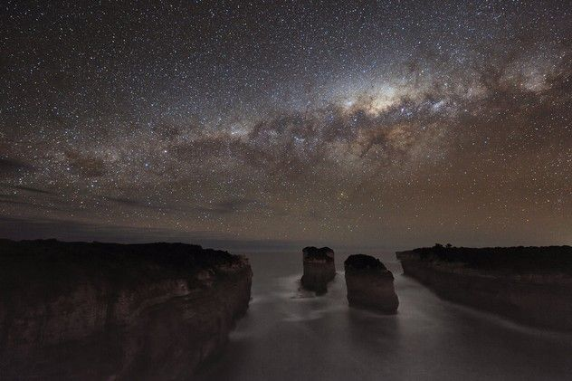 Milky Way Shadows Photo and caption by Alex Cherney  Far away from man-made lights the Port Campbell National Park (Victoria, Australia) is very dark on a moonless night. The stars in centre our Milky Way Galaxy are the most significant source of light which helped to create dark reflections on the water in the middle of the frame. : Stars, Australia, Alex Cherney, Space, Place, Photo, Alex O'Loughlin, Milky Way