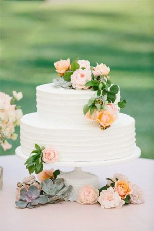 two tier white wedding cake styled with fresh flowers + leaves - brides of adelaide