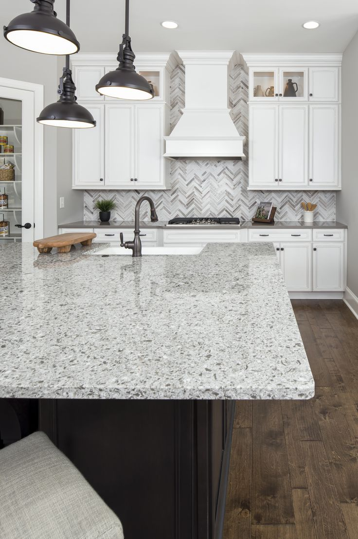 Herringbone mosaic backsplash, grey and white quartz countertops, and oil rubbed bronze pendant lights complete this rustic chic kitchen.  This Bel Aire model home at Massey is located in Fort Mill SC