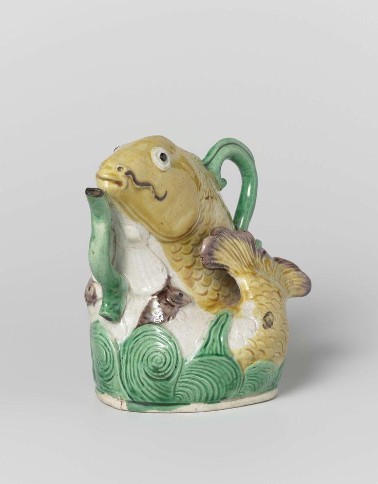 Anonymous | Kan in de vorm van een springende vis, Anonymous, 1680 - 1720 | Kan in de vorm van een springende vis. Een slanke, S-vormig gebogen tuit onder het lichaam, een gebogen oor op de rug; rond de voet een band met golven, aangegeven in laag-reliëf. Bedekt met gele, groene en bruine emails op het biscuit.