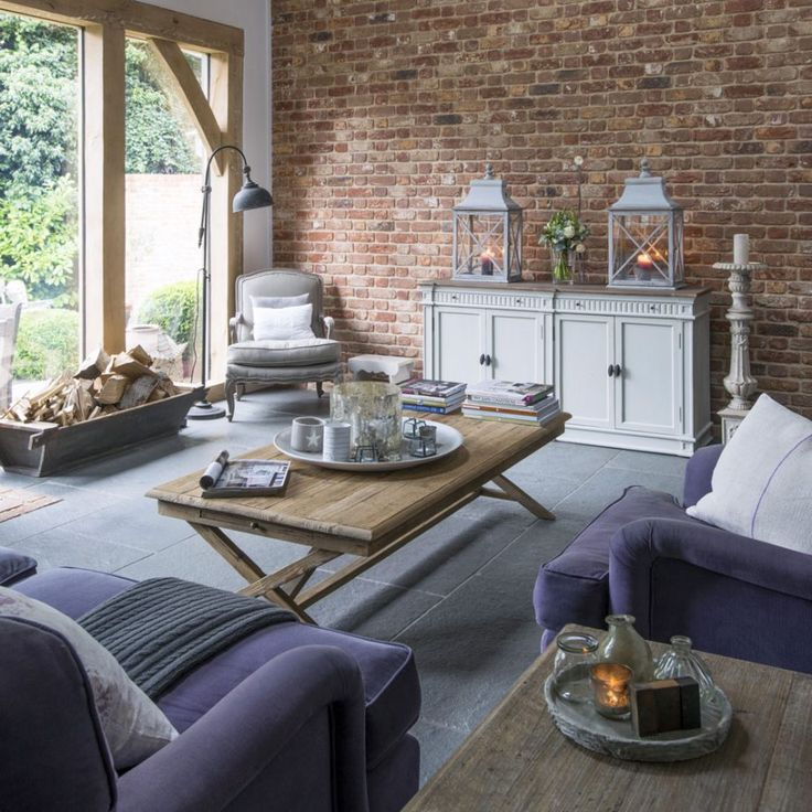 The massive brick wall has a barnlike feel, even though the house is a new-build. As well as creating a rustic look, the brickwork contrasts wonderfully with the deep purple of the upholstery. Cream furniture acts as a highlighter, creating a perfectly balanced scheme.