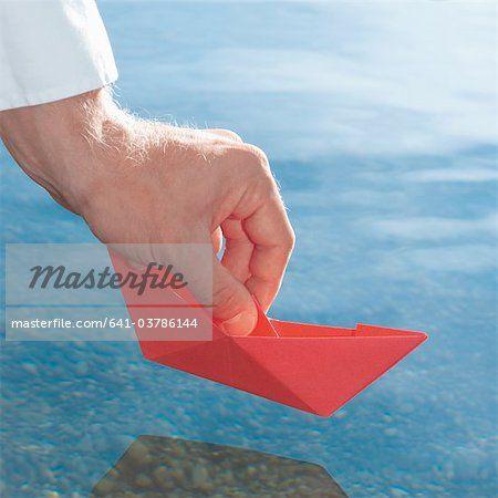 Germany, Human hand holding red origami boat  – Bild © Masterfile.com: Kreative Stock-Fotografie, Vektoren und Illustrationen für Internet-, Print- und Mobile-Nutzung