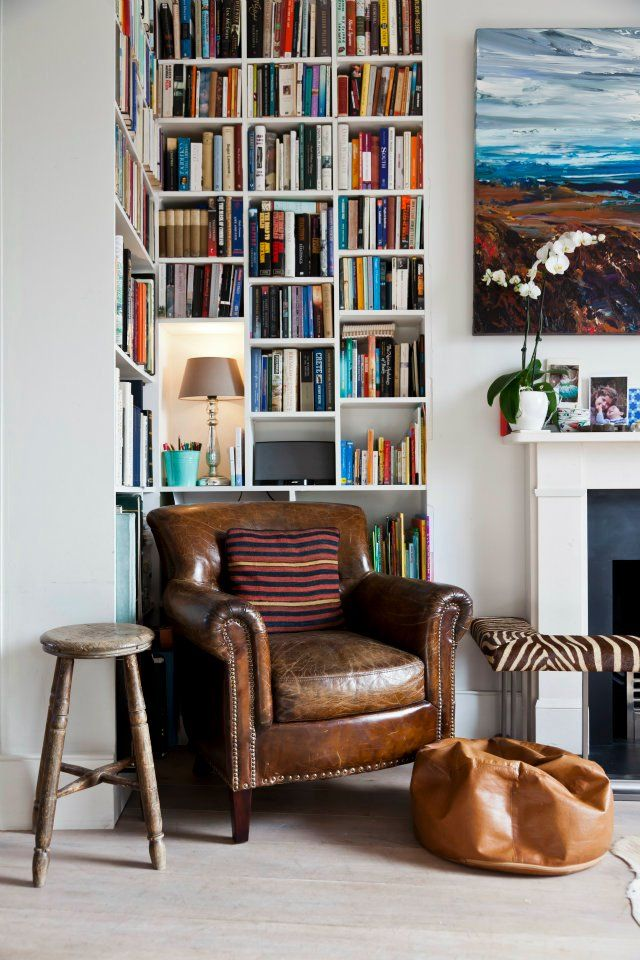 cosy interior. leather armchair and bookshelf