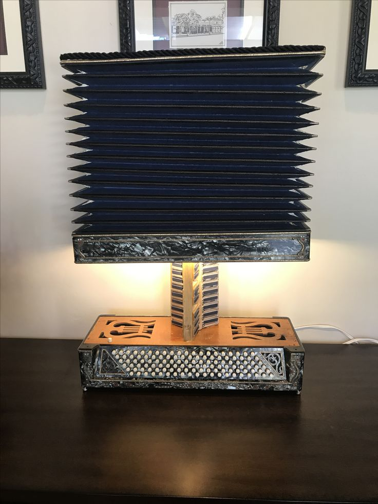 Accordion instrument repurposed to a lamp. LED light bar installed, and much of accordion body used to make lamp. Accordion button now activates the LED lights