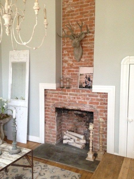 sherwin williams silver strand is a subtle blue gray colour with just a dob of green to soften it. Shown with red brick fireplace. This blog post shows 7 more fab colours. #sherwinwilliams #silverstrand #paint