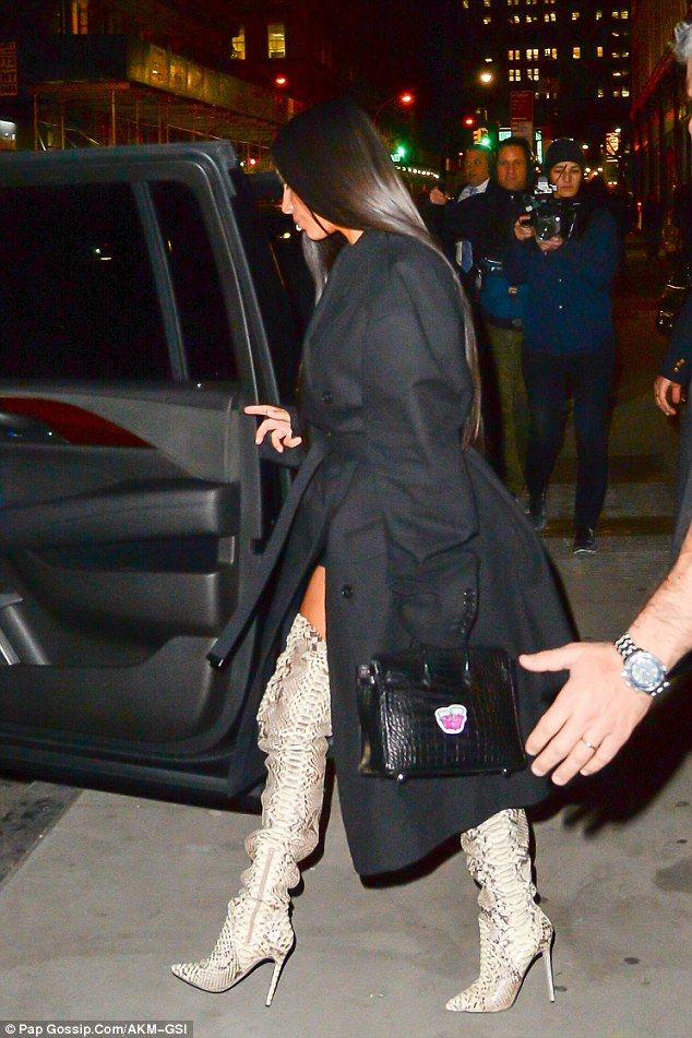 Leggy! Kim Kardashian shows off a bit of upper thigh in revealing trench and thigh-high boots while leaving an office building in New York City Thursday evening