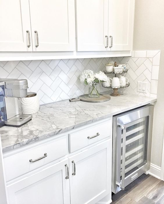 Small butler\'s pantry with herringbone backsplash tile and white quartzite  countertop. Away from the busy kitchen, nearer to the couch.