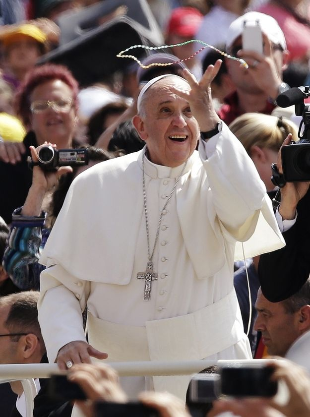 Pope Francis is cool. They're tossing him a rosary like beads at a Mardi Gras celebration. All he had to do was flash that loving smile.