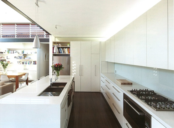 A bright, open island bench kitchen. White, white and more white with glass splashback.
