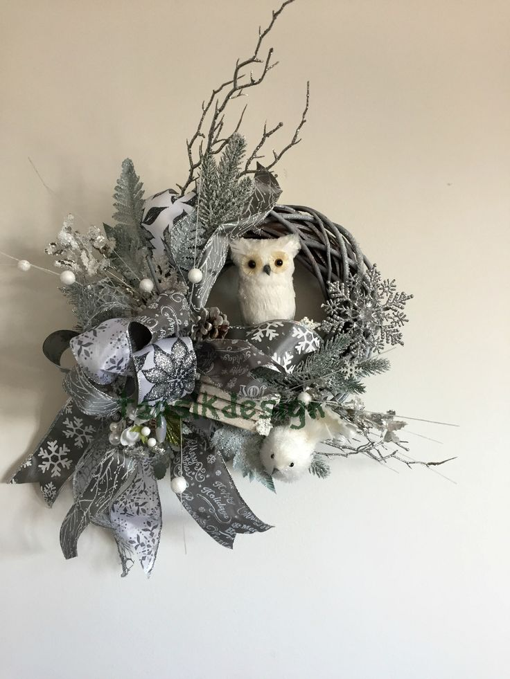 Christmas wreath. Owl. In the colors white-grey-silver. Full of artificial greenery, funky bow, sledge, snowflakes, bird, pinecones and of course an owl.