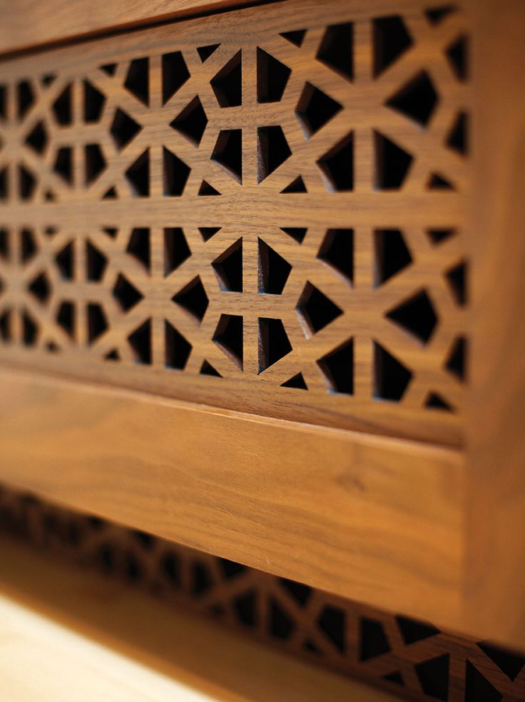 Air vents are cleverly concealed by custom laser-cut walnut in a Moroccan pattern.