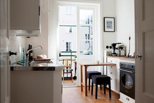 The designers for this small kitchen in Sweden built a pull-out table in the middle of the existing drawers. Now, it's the perfect spot for an intimate dinner for two. From Bolaget via The Kitchn   - HouseBeautiful.com