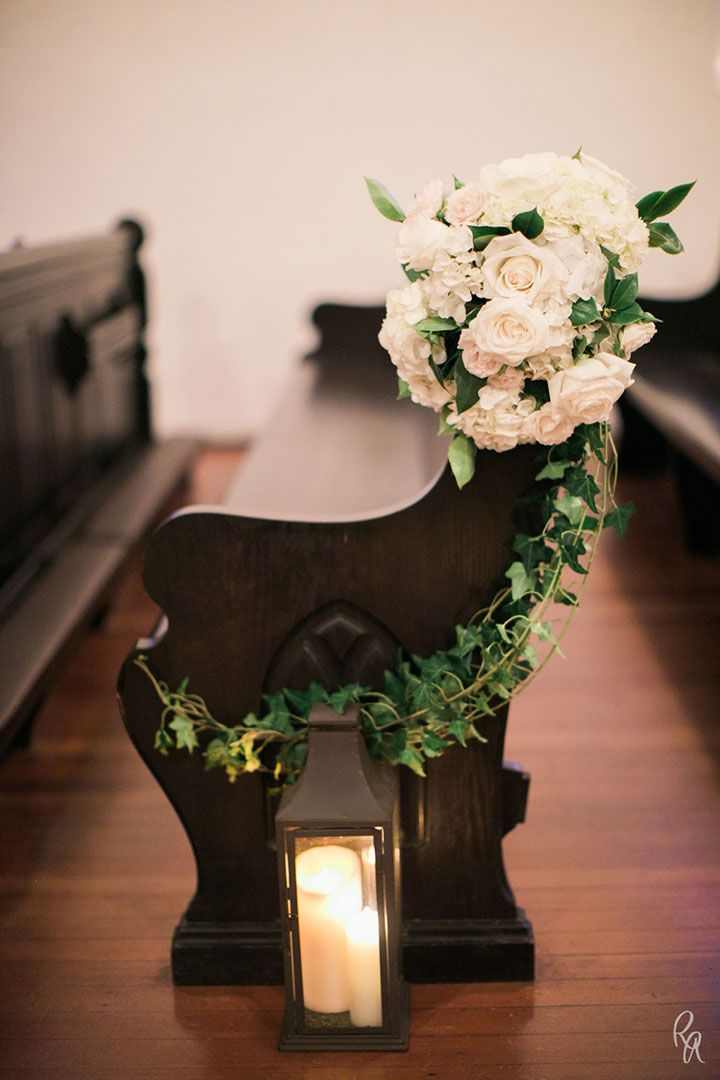 White roses and hydrangea sit atop a pew with curving ivy.