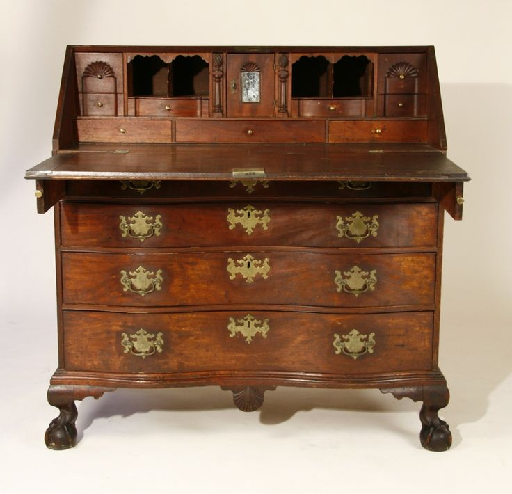"Reverse-serpentined Chippendale desk of mahogany with oversized ball and claw feet, perfectly-carved scallop shell center drop, oversized original brasses, blocked and shell-carved interior with three fans, carved flame-topped document drawers, and rare mirrored prospect door. 'As descended' condition, with original surface and great presence. North Shore, MA, probably Salem, c1775.  41 3/4"" width, 44"" ht. Obvious crack in the lid at one hinge."