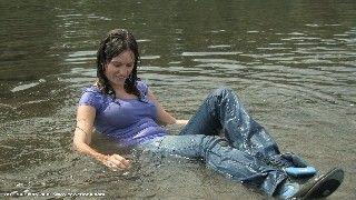 Une fille dans une rivière portant un T-shirt lavande, un jeans et chaussures de sport.