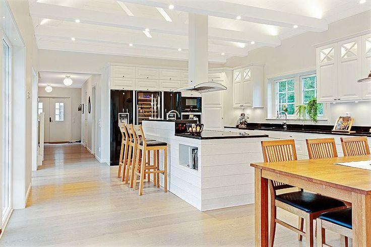 Kök med bjälkar i taket och öppet upp i nock. LUCKA: Meny vit | Ballingslöv LOCATION: Smakfullt New Englandhus i Höllviken