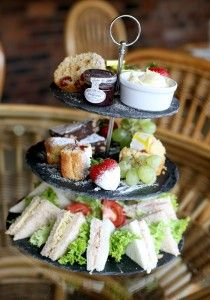 first tier: cucumber sandwiches second tier: grapes, raspberries, strawberries in cups third tier: donut holes, scones