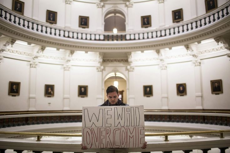 """Jacob Rubio holds a sign that reads """"We will overcome,"""" in the rotunda of the state Capitol shortly after the Electoral College cast their vote in Austin, Texas, Monday, Dec. 19, 2016. (Tamir Kalifa/AP)"""