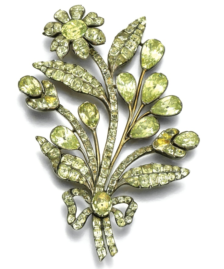 Chrysoberyl brooch, probably Portuguese, second half of the 18th century. Designed as a floral and foliate spray tied with a ribbon, set with foil backed cushion-, pear-shaped, oval and mixed-cut chrysoberyl