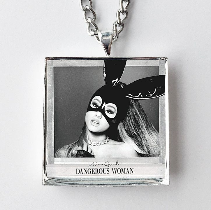 """This is a necklace featuring album art of the """"Dangerous Woman"""" record by Ariana Grande sealed in a silvertone metal setting. The album cover pendant is 1"""" and on a 20"""" long silvertone neck chain. The"""